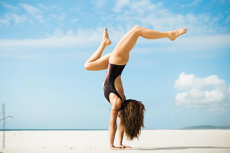 women in handstand with split legs on empty beach  by Tahl Rinsky for Stocksy United