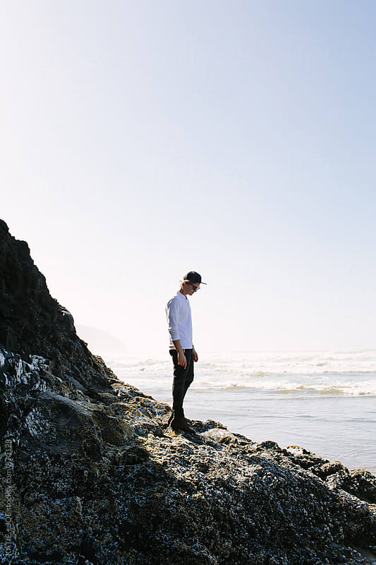 Man standing on rocks near the shore of the ocean on a sunny day by KATIE + JOE for Stocksy United