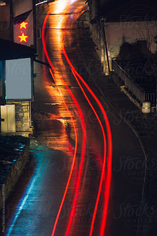 Car light trails on winding street by Pixel Stories for Stocksy United