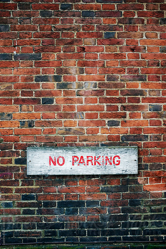 No parking sign on a red brick wall by James Ross for Stocksy United