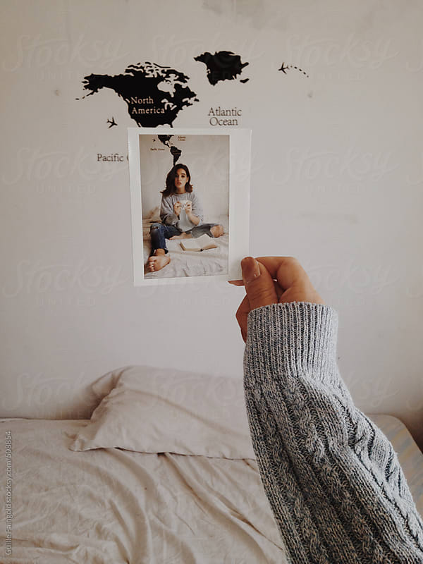 female holding her instant polaroid at her room by Guille Faingold for Stocksy United