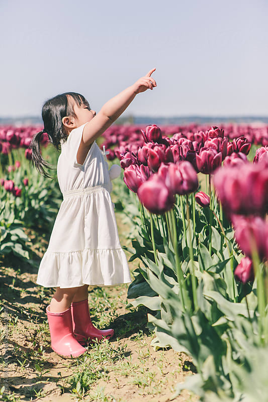 Asian girl outdoor in a tulip field pointing to the sky by Suprijono Suharjoto for Stocksy United