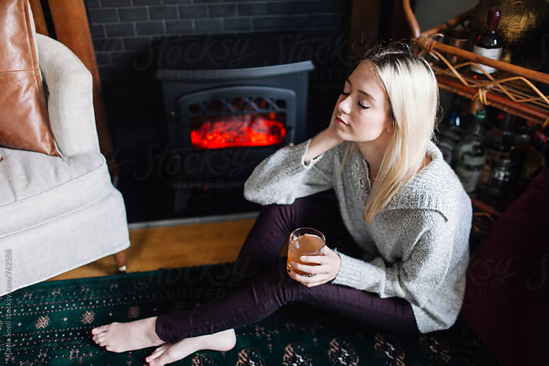 Young woman resting by the fire with a cocktail by Kayla Snell for Stocksy United