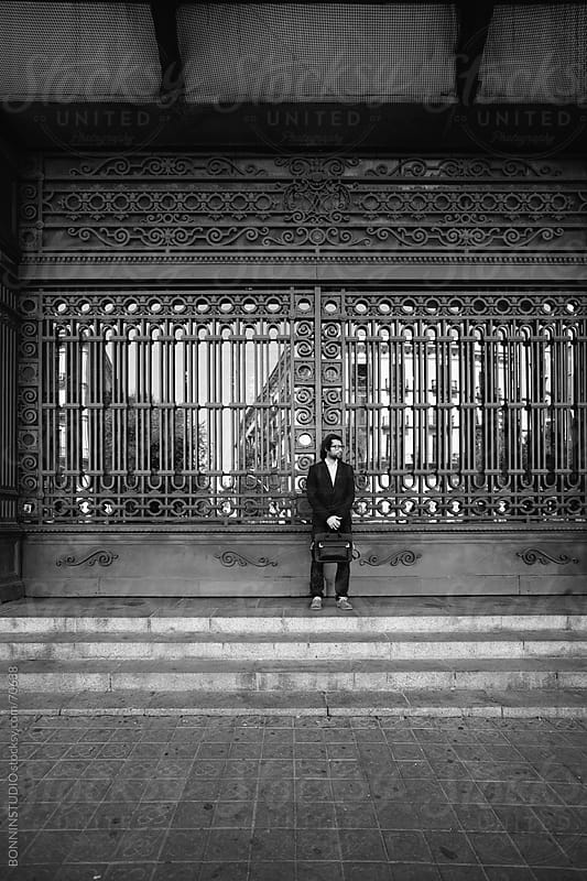 Young modern businessman waiting in front a big iron door on a train station. Barcelona. by BONNINSTUDIO for Stocksy United