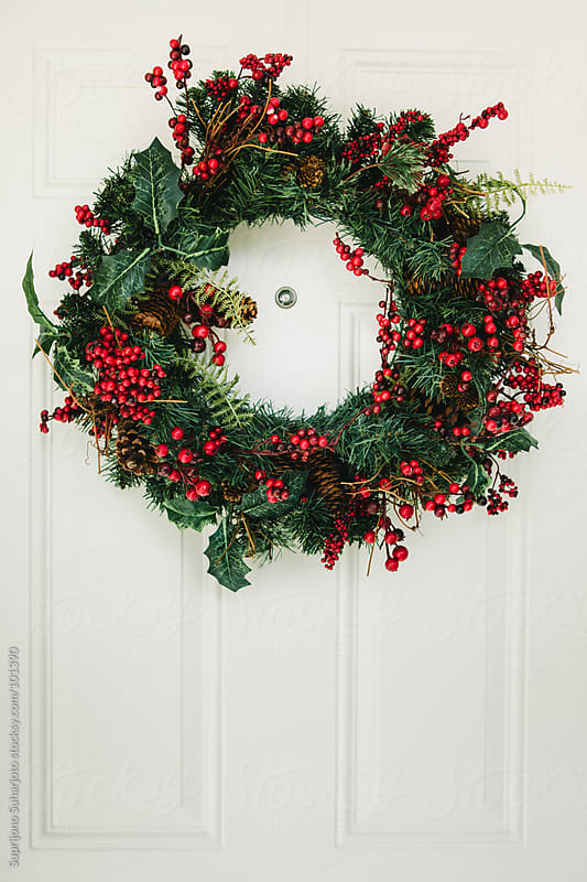 Christmas wreath hanging on the door by Suprijono Suharjoto for Stocksy United