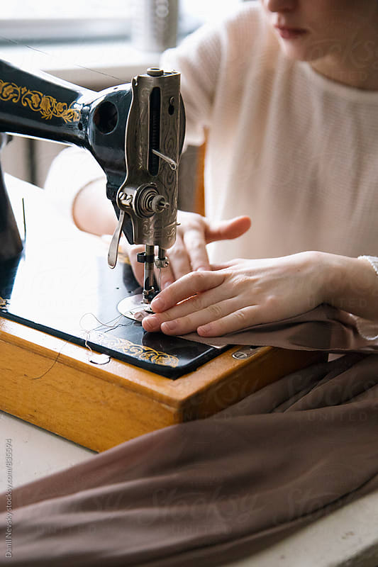Close-up of woman's hands working with vintage sewing machine by Danil Nevsky for Stocksy United