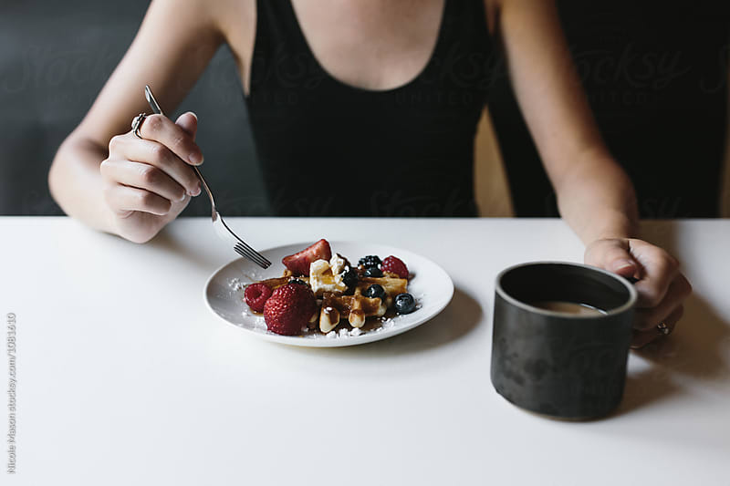 person eating waffle with fruit on top and holding mug of coffee by Nicole Mason for Stocksy United