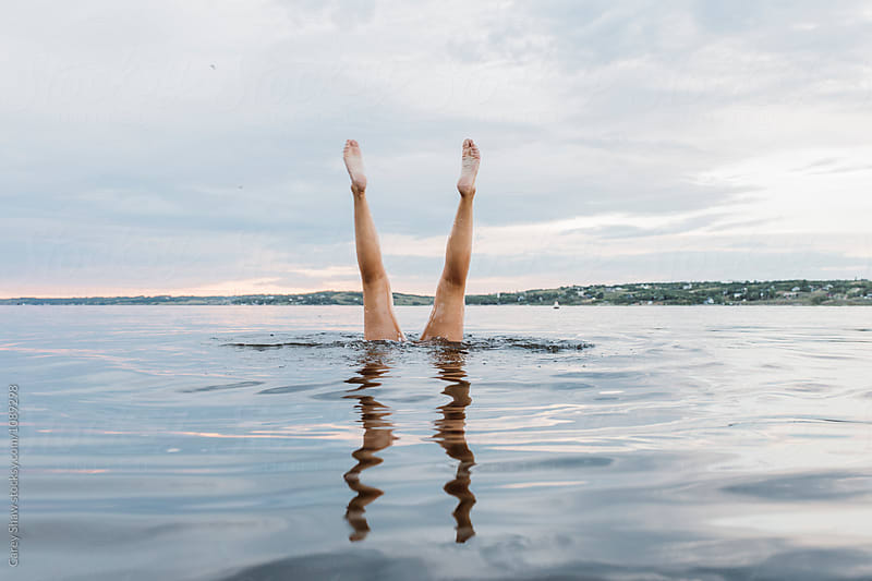 Swimmer doing handstands in the water by Carey Shaw for Stocksy United