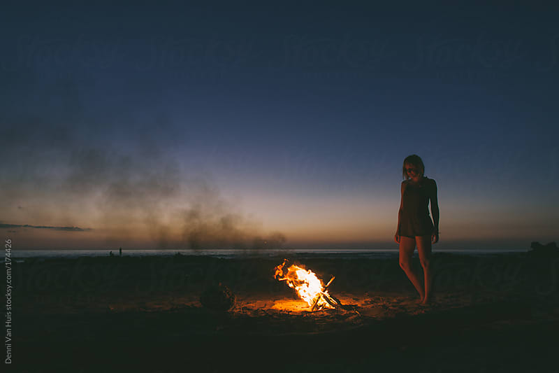 Woman enjoying the warmth of a bonfire on the beach under the stars by Denni Van Huis for Stocksy United