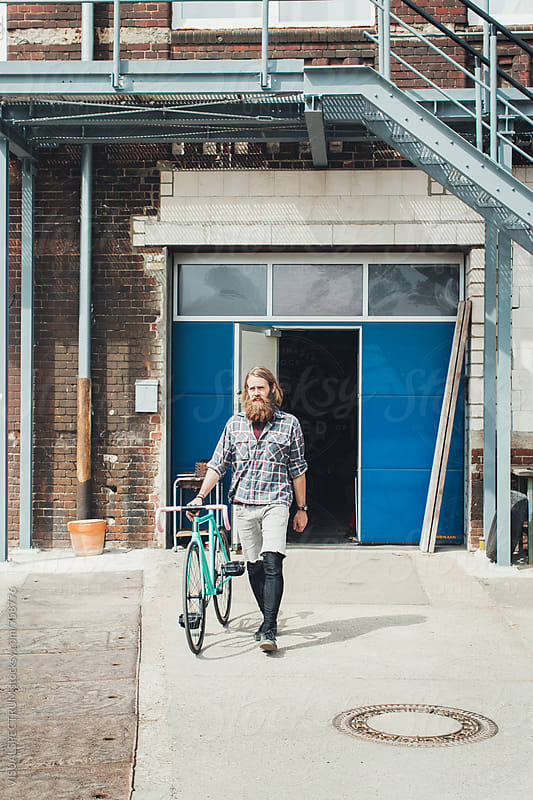Millennial Hipster Walking With Fixed Gear Bicycle in Bright Daylight by Julien L. Balmer for Stocksy United
