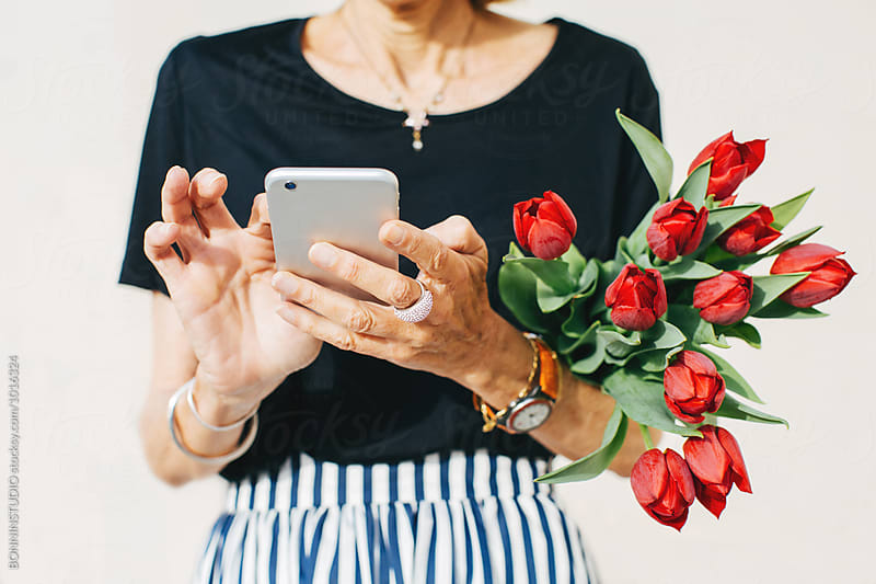 Closeup of a stylish senior woman holding red tulips using her phone outside.  by BONNINSTUDIO for Stocksy United