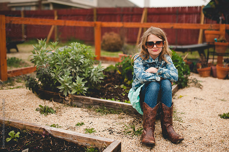 young girl sitting in the family garden by Courtney Rust for Stocksy United