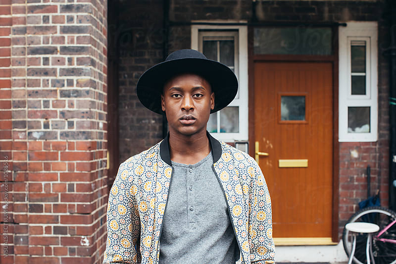 London Street Style - Outdoor Portrait of Young Fashionable Black Man Standing in Front of Working Class Home by Julien L. Balmer for Stocksy United