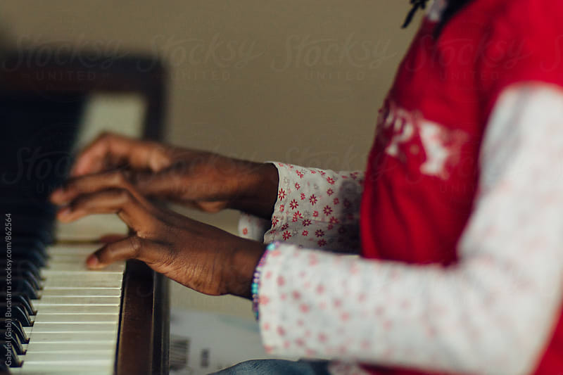 Hands of a black girl playing the piano by Gabriel (Gabi) Bucataru for Stocksy United