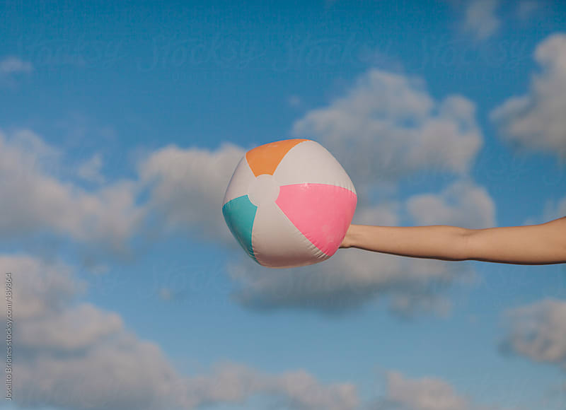 Young Woman's Hand Holding Inflatable Beach Ball against the Sky as Background by Joselito Briones for Stocksy United