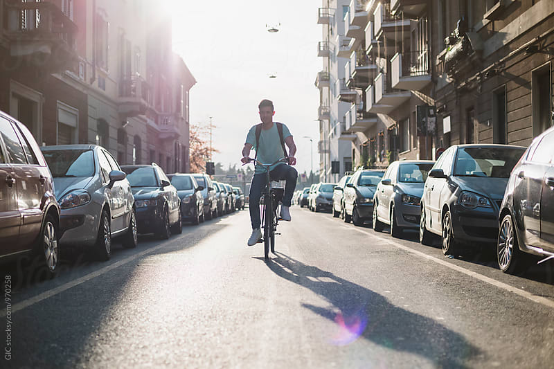 Asian man cycling in the city by Simone Becchetti for Stocksy United