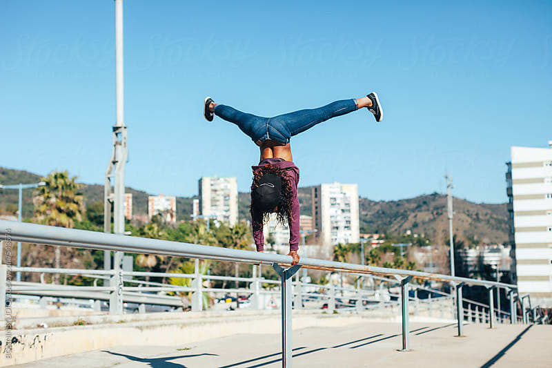 African american hip-hop style woman doing a handstand on a fence in a city. by BONNINSTUDIO for Stocksy United