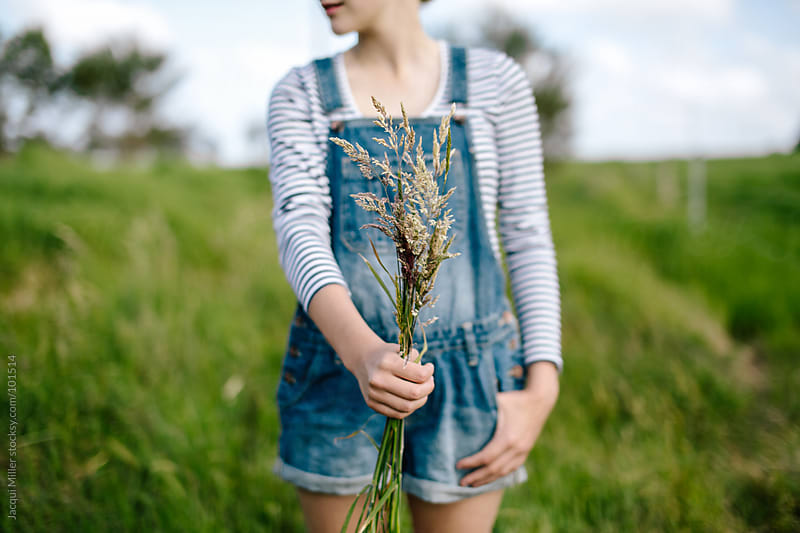 Girl holding long flowering grass in her hand by Jacqui Miller for Stocksy United