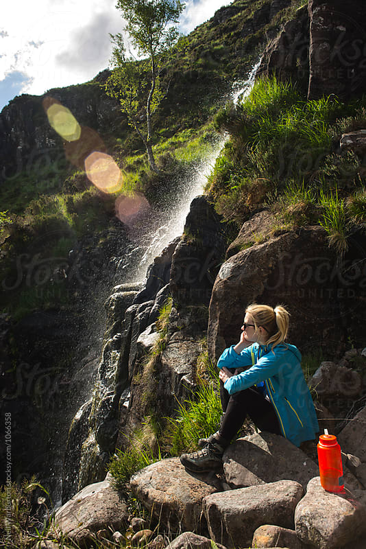 Female hiker resting by a waterfall by Neil Warburton for Stocksy United