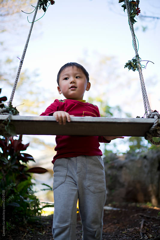 Kid standing in front of swing in forest by Lawren Lu for Stocksy United