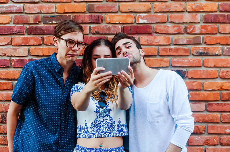 A group of friends taking their picture with a phone by Chelsea Victoria for Stocksy United