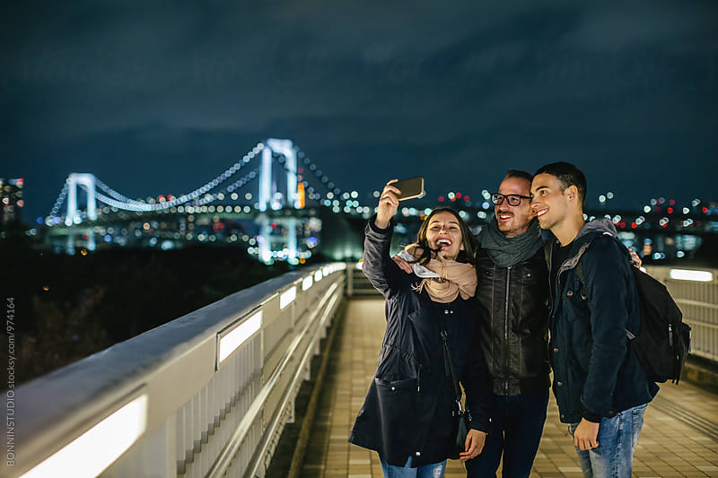 Tourist friends taking a selfie from Tokyo cityscape at night. by BONNINSTUDIO for Stocksy United