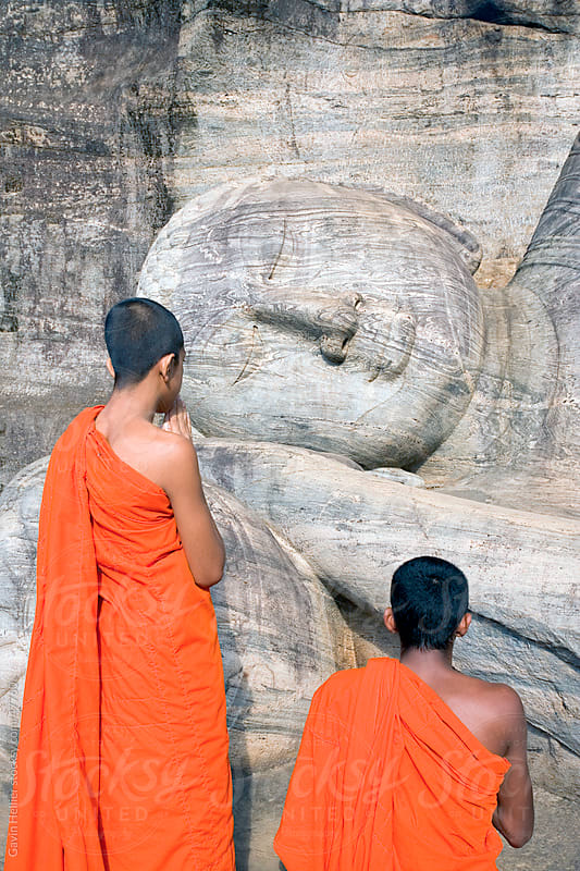 Monks praying at a rock-cut image of the Buddha in the Gal Vihara, Polonnaruwa (Polonnaruva), UNESCO World Heritage Site, Sri Lanka, Asia by Gavin Hellier for Stocksy United