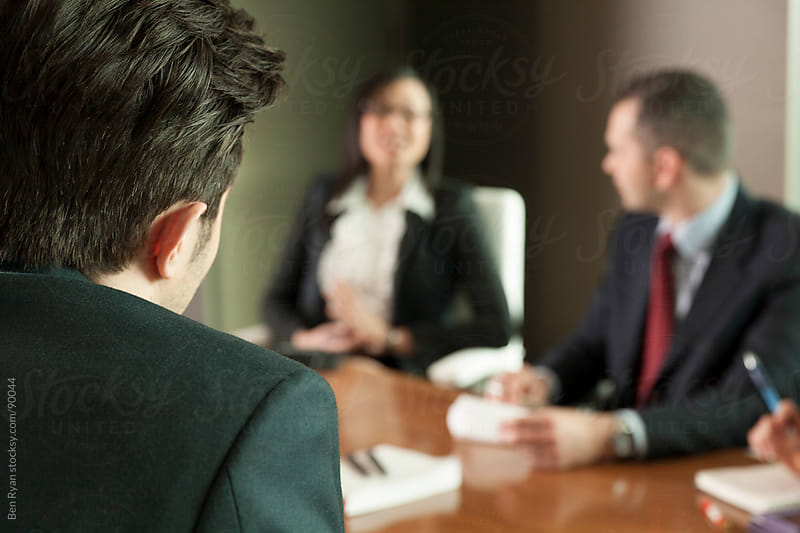 Looking over the shoulder of a young executive to two colleagues by Ben Ryan for Stocksy United