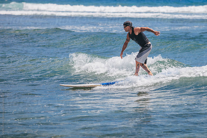 Surfer ridding a small wave in Hawaii by Shelly Perry for Stocksy United