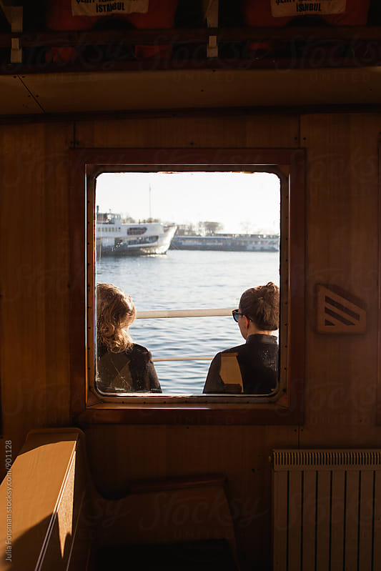 Tourists in Istanbul seen through a ferryboat window. by Julia Forsman for Stocksy United