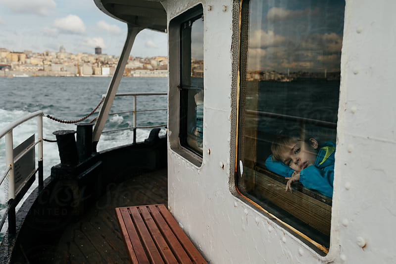 A boy gazes drowsily out of a ferryboat window as he crosses the Bosphorus Strait. by Julia Forsman for Stocksy United
