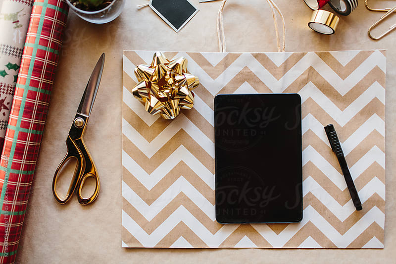 Making your holiday gift list by using a smart touch tablet  by Kristen Curette Hines for Stocksy United