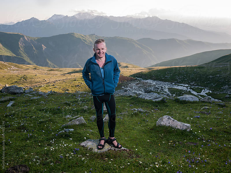 Young hiker standing on the grass with mountains in the background by Martin Matej for Stocksy United