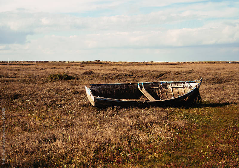 Boats on marshland by Helen Rushbrook for Stocksy United