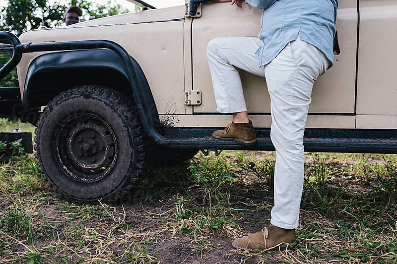 Man leaning on car on relaxing safari by Trent Lanz for Stocksy United