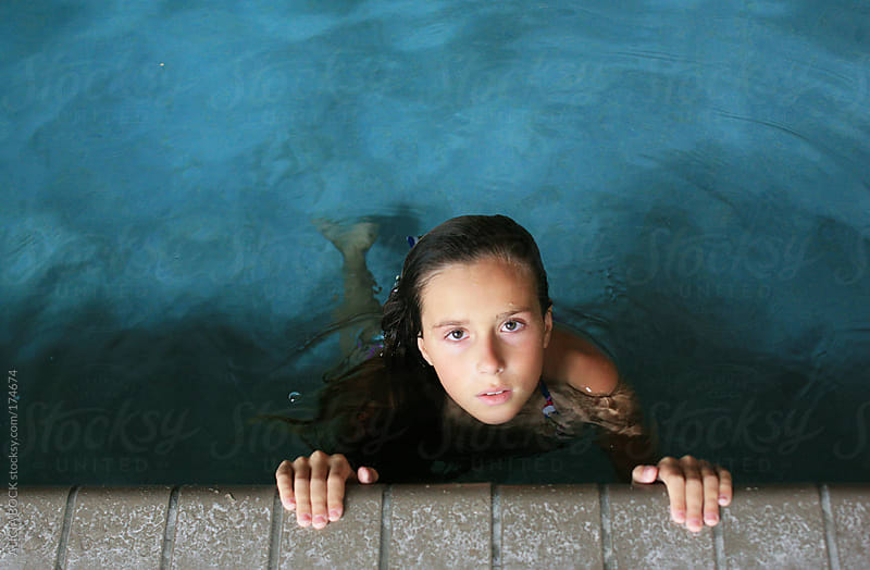 Girl Holding Onto the Edge of A Pool by ALICIA BOCK for Stocksy United