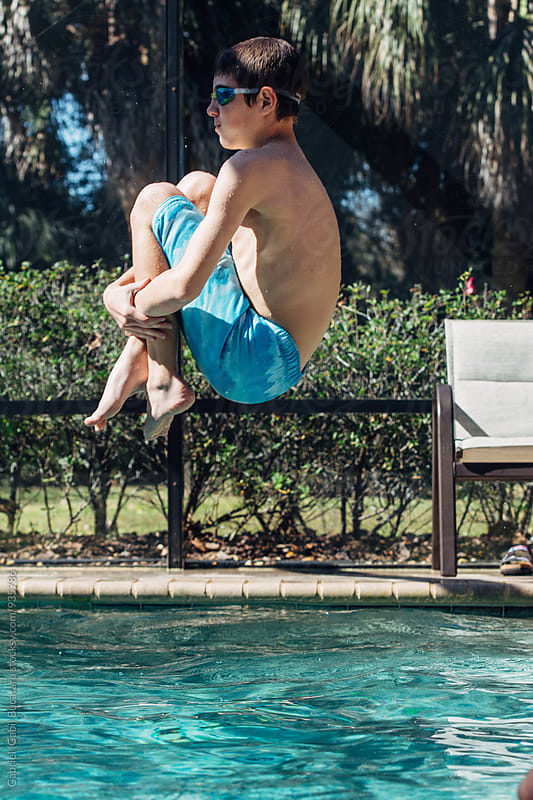Young boy jumping in a swimming pool by Gabriel (Gabi) Bucataru for Stocksy United