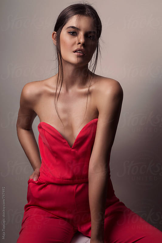 Young beautiful woman in red overall in studio by Maja Topcagic for Stocksy United