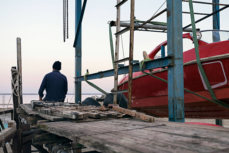 Back view of man on pier near red motorboat by Danil Nevsky for Stocksy United