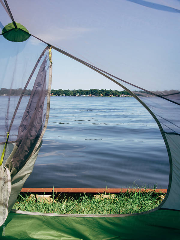Looking out at water through tent while camping on a lake by Jeremy Pawlowski for Stocksy United