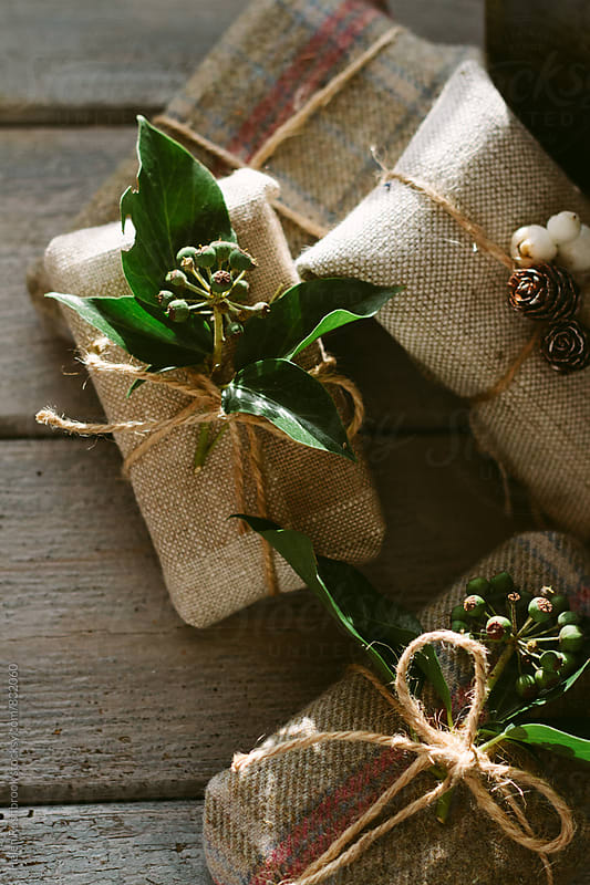 Christmas gifts wrapped in fabric and with natural details. by Helen Rushbrook for Stocksy United