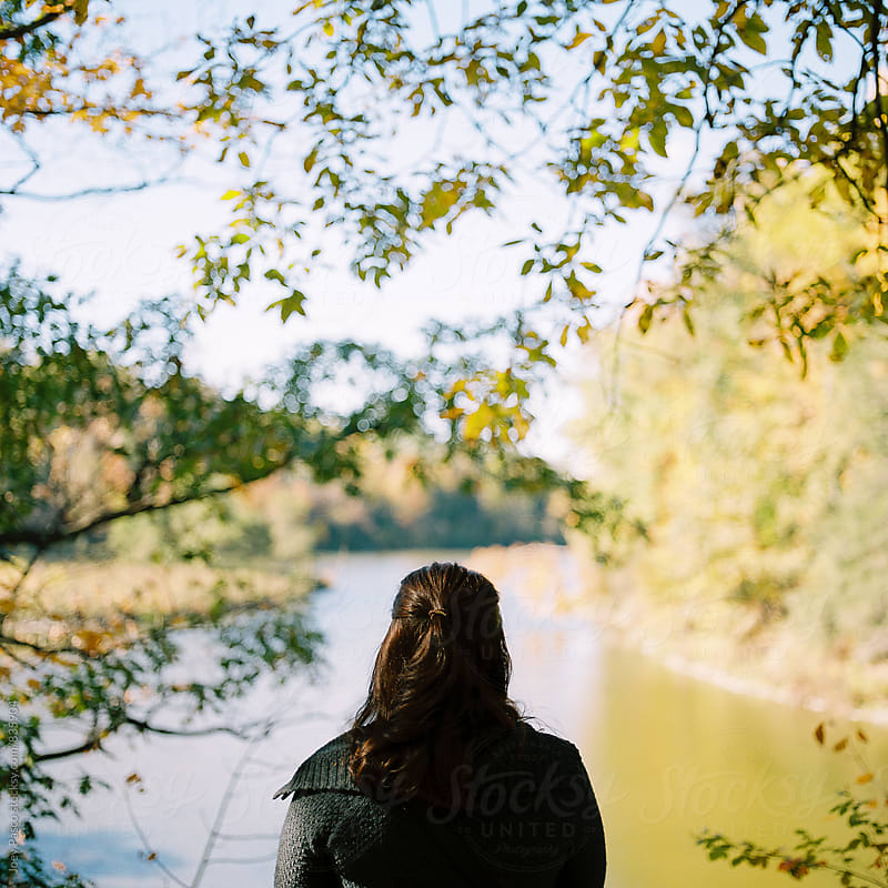 Woman stands in front of lake under shade of tree in autumn at midday by Joey Pasco for Stocksy United
