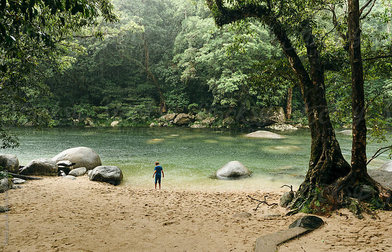Child standing near river playing in the rain in Australian forest by Trent Lanz for Stocksy United