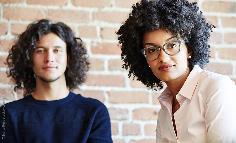 Close-up portrait of two millennials business people at work by Trinette Reed for Stocksy United