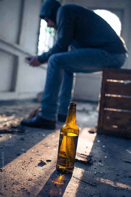 Depressed man sitting on a box with a bottle. by michela ravasio for Stocksy United