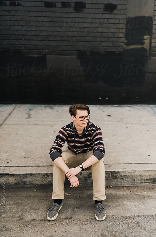 Young man sitting on sidewalk by Isaiah & Taylor Photography for Stocksy United