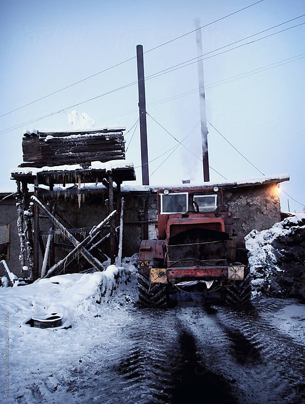 a bulldozer delivering coal to a heating station. by Amos Chapple for Stocksy United