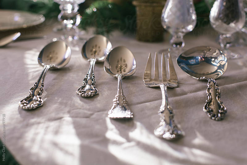 Silver serving utensils on a tablecloth at Thanksgiving. by Holly Clark for Stocksy United