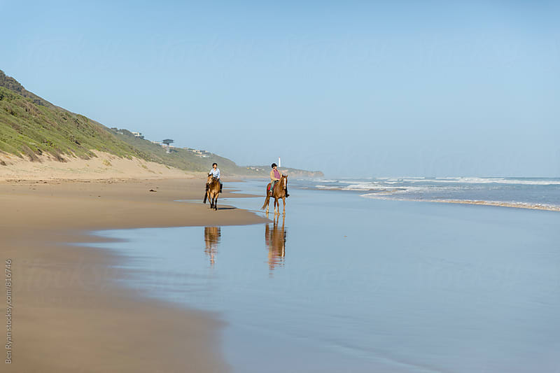 Senior male and female couple riding horses on isolated beach by Ben Ryan for Stocksy United
