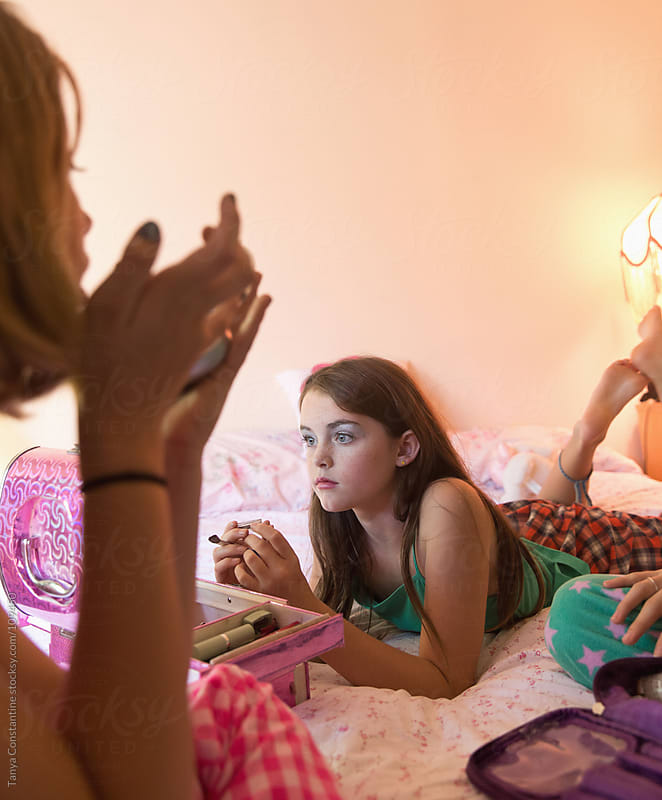 tween girls putting on make-up in their bedroom by Tanya Constantine for Stocksy United